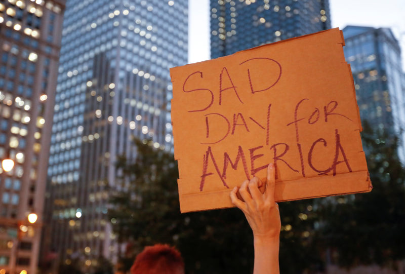 A protester holds a sign during a protest against Republican president-elect Donald Trump outside Trump International Hotel and Tower in Chicago, Illinois, U.S. November 9, 2016. REUTERS/Kamil Krzacznski - RTX2SWZM