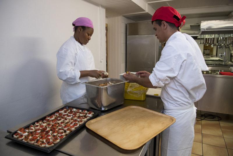 Integration in den Arbeitsmarkt entlastet die Sozialhilfe. Flüchtlinge arbeiten in einem Restaurant im Kanton Waadt. Foto: Jean-Christophe Bott (Keystone)
