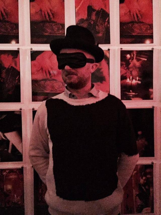 Der Galerist Adi Ehrat in vollem Ornat vor den ausgestellten Werken