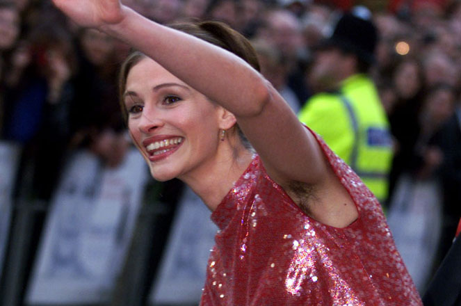 U.S. actress Julia Roberts waves as she arrives at the premiere of the new film Notting Hill in Lond..