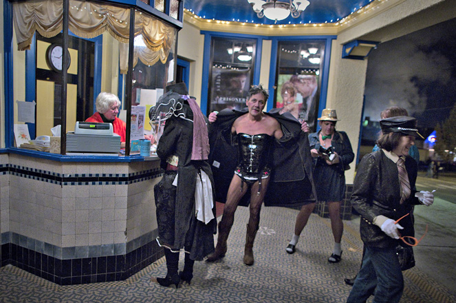 Cinema owner Ann Nelson sits in the ticket booth, as people in costume arrive to watch a late night screening of the
