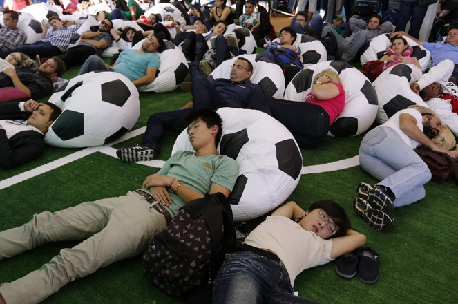Passengers relax as they watch the 2014 World Cup Group F soccer match between Iran and Nigeria, at Guarulhos International Airport