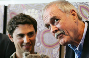 British comedian John Cleese reacts as he poses with 'McAuley' the Koala at Taronga Zoo in Sydney