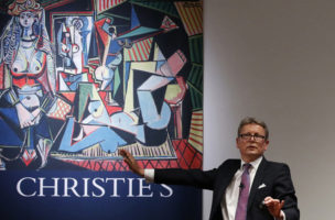 Christie's auctioneer and Global President Jussi Pylkkanen gestures during bidding for Pablo Picasso's Women of Algiers (Version O), (1955), shown behind him in a poster, which sold for $179.4 million, making it the most expensive artwork sold at auction, during a sale of 20th century art at Christie's Rockefeller Center in New York, Monday, May 11, 2015.  Experts say the once unthinkable prices are driven by artworks' investment value and by wealthy new and established collectors seeking out the very best works. (AP Photo/Kathy Willens)