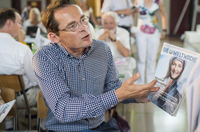 Nationalratskandidat und Chefredaktor der Weltwoche Roger Koeppel zeigt einem Delegierten ein Ausgabe der ''Weltwoche?? der Delegiertenversammlung der SVP am Samstag, 4. Juli 2015 in Kerns. (KEYSTONE/Ennio Leanza)