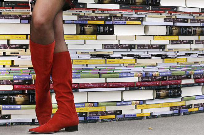 A woman with red boots stands next to books on the second day of the Book Fair that will be opened later the day in Frankfurt, Germany, Thursday, Oct. 11, 2012. New Zealand is this year's guest of honor. (AP Photo/Michael Probst)