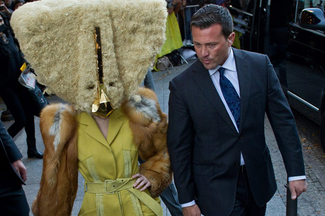 epa03922570 US singer Lady Gaga (L), wearing a costume, arrives in Berlin, Germany, 24 October 2013. Lady Gaga came to Berlin to present her new album 'Artpop'. The man at her right side is identified.  EPA/Ole Spata