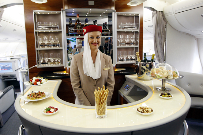 A flight attendant poses behind the bar in the rear of the business class section of Emirates' Airbus A380 after the jet arrived on its maiden flight at John F. Kennedy International Airport in New York August 1, 2008. Airbus's A380 superjumbo touched down in New York on Friday, marking the first commercial arrival of the giant, double-decker passenger plane on U.S. soil.  REUTERS/Chip East  (UNITED STATES)   FOR BEST QUALITY IMAGE: ALSO SEE GM1E57T038801 - RTR20JWF