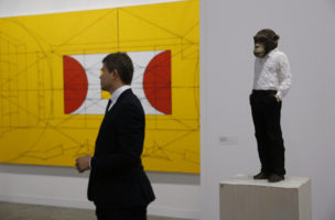 "A stands near  artwork ""Man with monkey head"", right, created by German artist Stephan Balkenhol during the VIP preview of the art fair ""Art Basel"" in Hong Kong, Tuesday, March 22, 2016. Gold-plated metal cubes, tapestries embroidered by unknown North Korean artisans and bales of cardboard waste are among the highlights of the Art Basel Hong Kong fair kicking off this week. (AP Photo/Kin Cheung)"