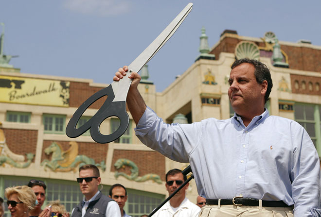 New Jersey Governor Chris Christie (R) holds up a giant pair of scissors after taking part in a ribbon-cutting ceremony during a series of Memorial Day weekend stops along the Jersey shore to mark the start of the summer tourism season, in Asbury Park, New Jersey May 23, 2014. REUTERS/Eduardo Munoz (UNITED STATES - Tags: POLITICS ANNIVERSARY TRAVEL) - RTR3QLWP