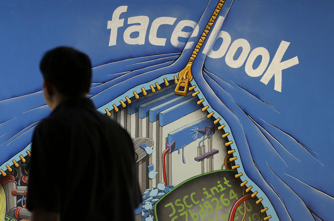 FILE - In this June 11, 2014, file photo, a man walks past a mural in an office on the Facebook campus in Menlo Park, Calif. On Thursday, May 12, 2016, Facebook pulled back the curtain on how its Trending Topics feature works, a reaction to a report that suggested Facebook downplays conservative news subjects. (AP Photo/Jeff Chiu, File)