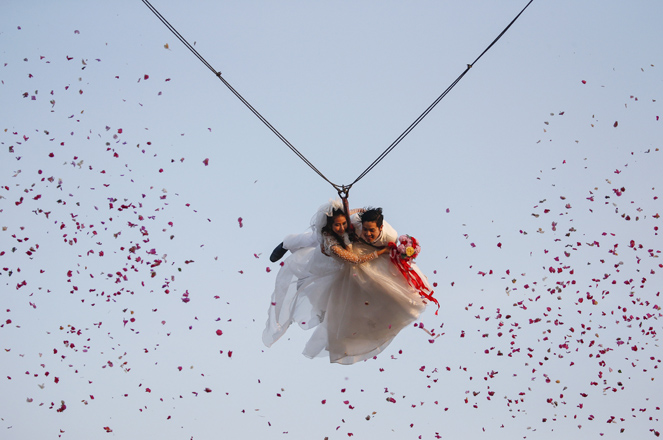 Bride Jintara Promchat, 28, and groom Kittinant Suwansiri, 29, fly while attached to cables during a wedding ceremony ahead of Valentine's Day at a resort in Ratchaburi province, Thailand, February 13, 2016. Four Thai couples took part in the wedding ceremony arranged by the resort. REUTERS/Athit Perawongmetha - RTX26Q9U