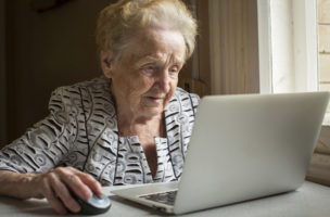 An elderly woman sitting at the table and types on laptop.