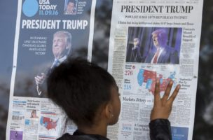 epa05624446 An African American child looks at election coverage on the front pages of today's newspapers on display outside the Newseum in Washington, DC, USA, 09 November 2016. The victory of Republican presidential candidate Donald Trump surprised many in the country after weeks of polling data appeared to indicate that Hillary Clinton was poised to win.  EPA/MICHAEL REYNOLDS