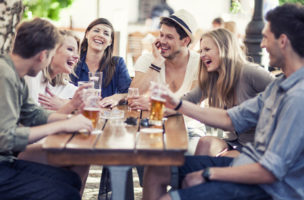 Group of young cheerful people having fun drinking beer outdoors.