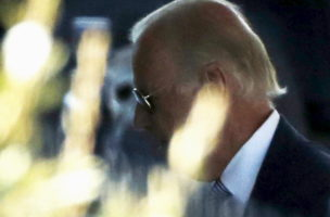 U.S. Vice President Joe Biden (C) can be seen through hedges as he arrives to attend the presidential daily briefing at the White House in Washington August 24, 2015. More prominent Democrats on Sunday cracked open the door for Biden to enter the race for the Democratic presidential nomination as party front-runner Hillary Clinton battled questions over her use of a private email server. REUTERS/Jonathan Ernst - RTX1PH1U