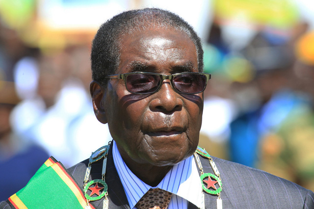 Zimbabwean President Robert Mugabe inspects the guard of honour during a ceremony in Harare, Monday Aug. 10, 2015, honouring thousands of fighters who died in a 1970s Bush war against colonialism. Mugabe, in his first public comments about the popular lion named Cecil, says his compatriots failed in their responsibility to protect the lion that was killed by an American in an allegedly illegal hunt. (AP Photo/Tsvangirayi Mukwazhi)