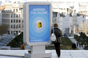 A woman leans on a board with a telephone in central Brussels, Belgium, January 8, 2016. The phone was installed in a new campaign by the city's tourism board, and designed to allow tourists to call Brussels residents to ask about the city's security status after its lockdown late last year.   REUTERS/Francois Lenoir - RTX21JRC
