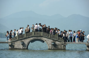 Visitors walk on a bridge on West Lake during China's golden week holiday in Hangzhou, Zhejiang Province, China, October 2, 2016. Picture taken October 2, 2016. REUTERS/Stringer ATTENTION EDITORS - THIS IMAGE WAS PROVIDED BY A THIRD PARTY. EDITORIAL USE ONLY. CHINA OUT.     - RTSQIKW