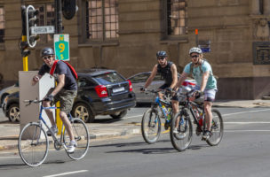 Johannesburg, South Africa - September, 7th 2013: Three cyclists cycling through Johannesburg city centre on Harrison street. The old Edwardian Standard Bank building seen in the background.