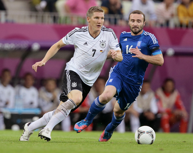 Germany's Bastian Schweinsteiger, left, and Greece's Dimitris Salpigidis go for the ball  during the Euro 2012 soccer championship quarterfinal match between Germany and Greece in Gdansk, Poland, Friday, June 22, 2012. (AP Photo/Ivan Sekretarev)