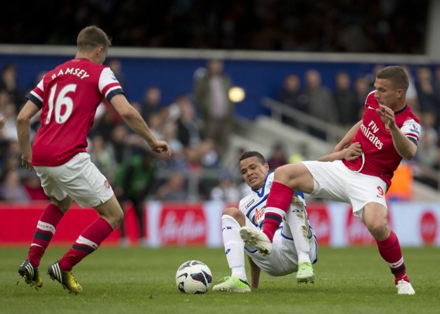 Queens Park Rangers' Jermaine Jenas, centre attempts to clear the ball from Arsenal's Lukas Podolski, right, and teammate Aaron Ramsey, during their English Premier league soccer match at Rangers' Loftus road stadium in London, Saturday, May  4, 2013. (AP Photo/Alastair Grant)