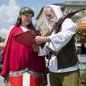 Helvetia et Guillaume Tell signent l'initiative  «Monnaie pleine»   sur la place fédérale à Berne, en juin 2014. Image/ Gian Ehrenzeller/Keystone
