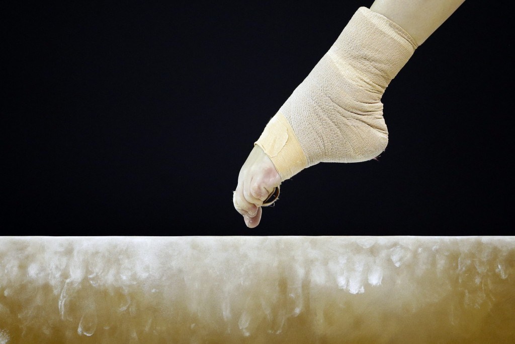 A bandaged foot from the United States' Rachel Gowey touches the beam during women's artistic gymnastics team competition in the Pan Am Games in Toronto, Sunday, July 12, 2015. (AP Photo/Gregory Bull)
