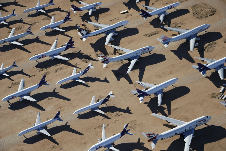 Old airplanes, including British Airways and China Airlines Boeing 747-400s and FedEx planes, are stored in the desert in Victorville, California March 13, 2015. Last year, there were zero orders placed by commercial airlines for new Boeing 747s or Airbus A380s, reflecting a fundamental shift in the industry toward smaller, twin-engine planes. Smaller planes cost less to fly than the stately, four-engine jumbos, which can carry as many as 525 passengers. Picture taken March 13, 2015. To match Insight AEROSPACE-JUMBO REUTERS/Lucy Nicholson