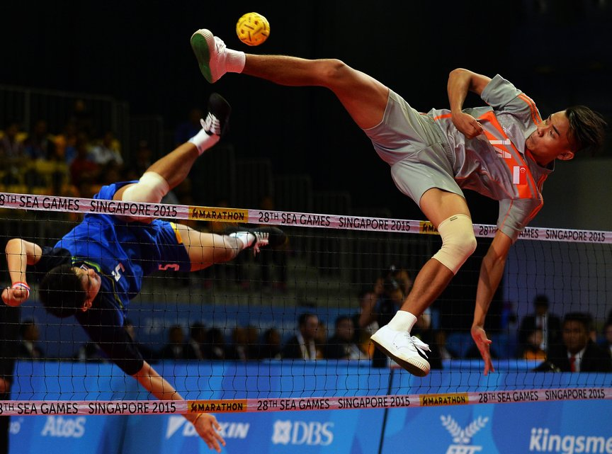 Muhammad A'fif of Singapore (R) jumps for the ball against Pornchai Kaokaew of Thailand (L) during the men's team sepaktakraw preliminary round match at the 28th Southeast Asian Games (SEA Games) in Singapore on June 8, 2015. AFP PHOTO / MOHD FYROL