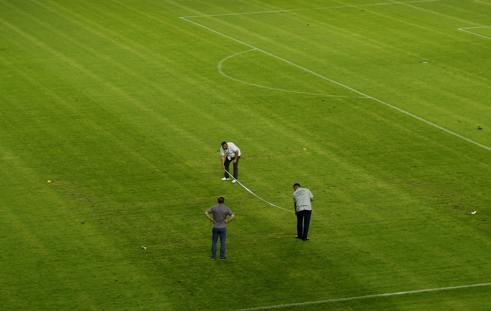 Police officers are seen on a pitch where the faint pattern of a swastika (L) is seen after the game between Croatia against Italy in Euro 2016 Group H qualifying soccer match at the Poljud Stadium in Split, Croatia, June 12, 2015. Croatia's 1-1 Euro 2016 qualifying draw at home to Italy was marred by a racist incident when a swastika cross appeared on the pitch in a match played behind closed doors on Friday. Imprinted into the grass of the Poljud stadium, the swastika was noticeable in the first half of the Group H fixture played without any fans present after the Croatians had been given a one-match ban for prior offences.  REUTERS/Antonio Bronic TPX IMAGES OF THE DAY      - RTX1GAQJ