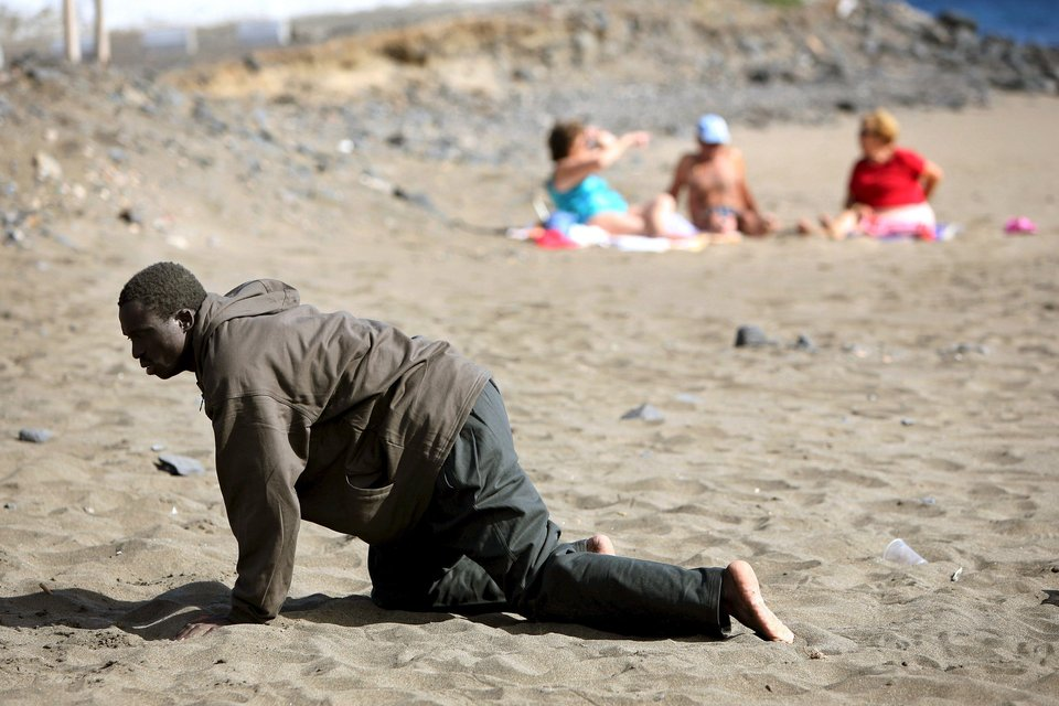 "A would-be immigrant crawls after his arrival on a makeshift boat on the Gran Tarajal beach in Spain's Canary Island, in this May 5, 2006 file photo. Italy stepped up calls for a change to European asylum rules on Sunday as neighbouring states tightened border controls, turning back African migrants and leaving hundreds stranded at the frontier in northern Italy.  REUTERS/Juan Medina/Files ATTENTION EDITORS - THIS PICTURE IS PART OF THE PACKAGE ""IN PLAIN SIGHT"". TO FIND ALL 9 IMAGES SEARCH 'MIGRANT EUROPEAN'.      TPX IMAGES OF THE DAY           TPX IMAGES OF THE DAY"