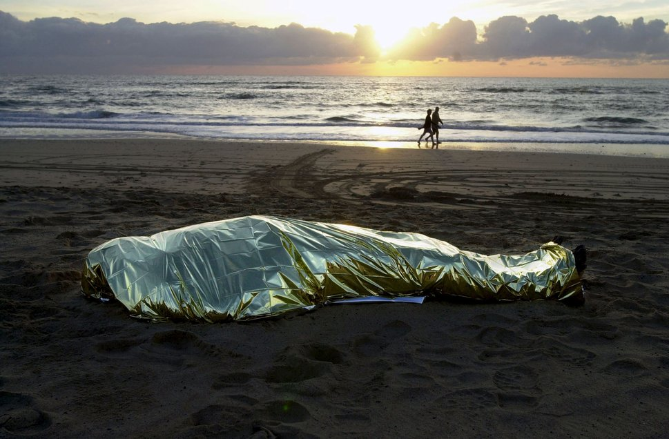 "The body of a dead immigrant, who drowned after his makeshift boat capsized, lies covered on El Matorral beach in Fuerteventura, Spain, as beachgoers walk along in the background, in this January 1, 2003 file photo. Italy stepped up calls for a change to European asylum rules on Sunday as neighbouring states tightened border controls, turning back African migrants and leaving hundreds stranded at the frontier in northern Italy.  REUTERS/Juan Medina/Files ATTENTION EDITORS - THIS PICTURE IS PART OF THE PACKAGE ""IN PLAIN SIGHT"". TO FIND ALL 9 IMAGES SEARCH 'MIGRANT EUROPEAN'.      TPX IMAGES OF THE DAY"