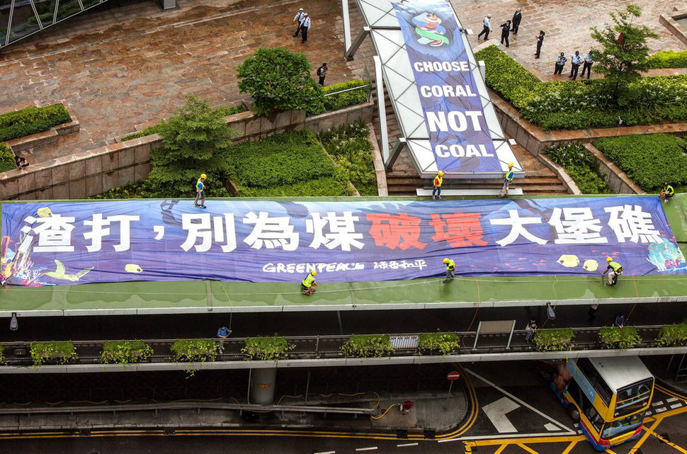 epa04814946 Greenpeace activists display a 'Choose Coral Not Coal' banner outside the flagship branch of Hong Kong's Standard Chartered Bank in the city's financial district, during a protest calling on the bank to withdraw its financing of the controversial Carmichael coal mine in Australia's Galilee Basin, in Hong Kong, China, 23 June 2015.  EPA/ALEX HOFFORD