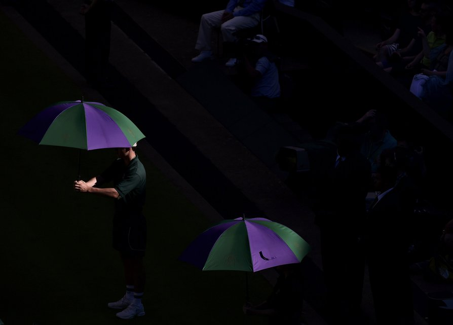 Ball boys hold umbrellas on Centre Court at the Wimbledon Tennis Championships in London, June 30, 2015.   REUTERS/Toby Melville TPX IMAGES OF THE DAY