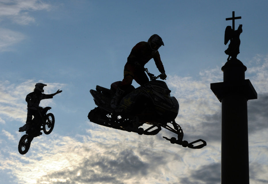Athletes jump during the Moto freestyle-battle Adrenaline FMX Riders in front of the Alexander Column on the Dvortsovaya Square in St. Petersburg on July 4, 2015. AFP PHOTO / OLGA MALTSEVA