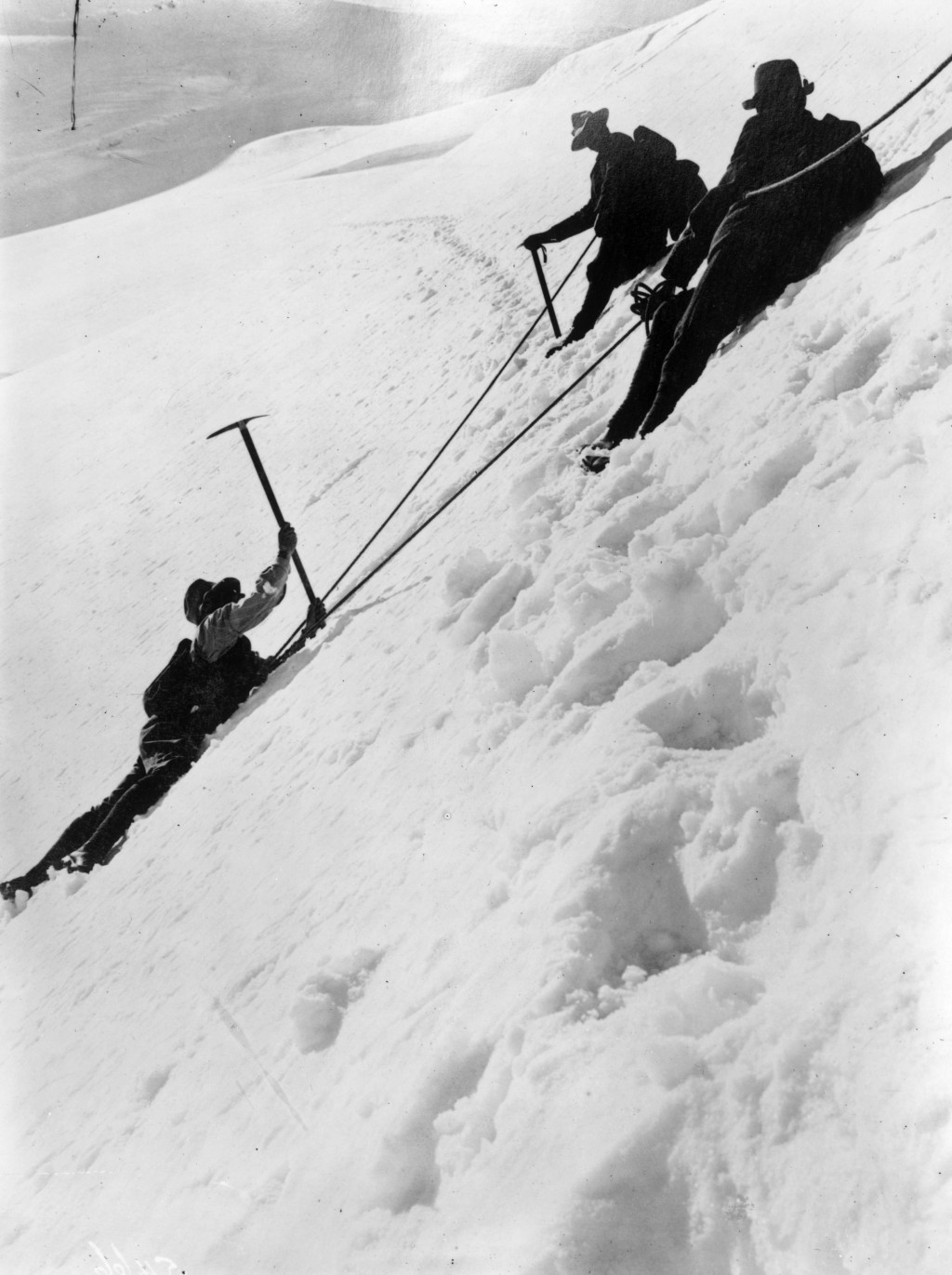 December 1910:  Climbers using ropes and pickaxes to climb a snowy bank in the Alps.  (Photo by Topical Press Agency/Getty Images)