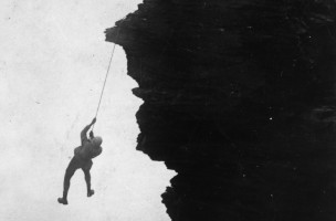 circa 1900:  A rock climber swinging on a rope as he is hauled up a cliff face.  (Photo by Hulton Archive/Getty Images)