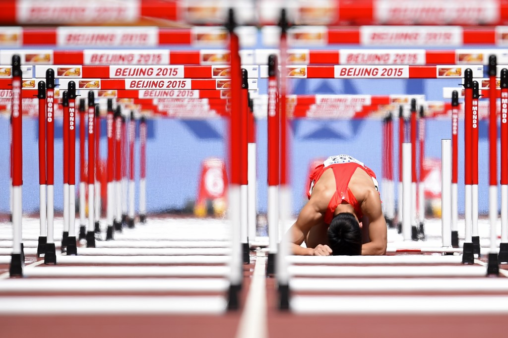 """China's Zhang Honglin reacts after falling during the men's 110 metres hurdles athletics event at the 2015 IAAF World Championships at the """"Bird's Nest"""" National Stadium in Beijing on August 26, 2015.  AFP PHOTO / OLIVIER MORIN"""