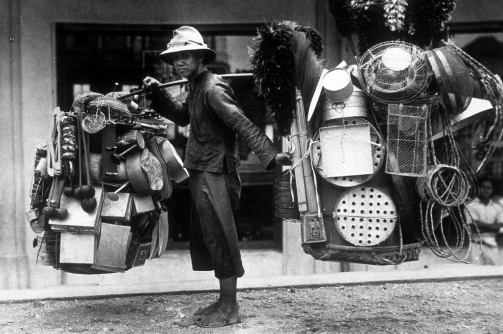 circa 1935: A man selling hardware from the baskets on his shoulders on the street in Bangkok. (Photo by Hulton Archive/Getty Images)