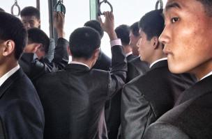 North Korean men on an airport transport bus headed to the Air Koryo flight for Beijing. (AP Photo/David Guttenfelder)