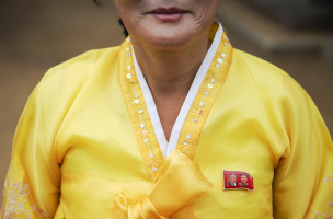 A woman in traditional clothes wears a pin showing North Korea's founder Kim Il-sung (L) and former leader Kim Jong-il, on her dress as she welcomes foreign reporters to a temple during a government organised tour just outside Pyongyang October 8, 2015. North Korea is getting ready to celebrate the 70th anniversary of the founding of its ruling Workers' Party of Korea on October 10.  REUTERS/Damir Sagolj - RTS3JR6