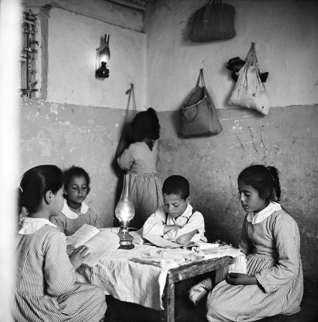 UNRWA Archive - Ausstellung Photobastei - BILDSEITE Kinder machen in Beach Camp, Gaza, Hausaufgaben im Licht einer Öllampe. © 1952 Fotografie aus dem UNRWA-Archive von Jack Madvo