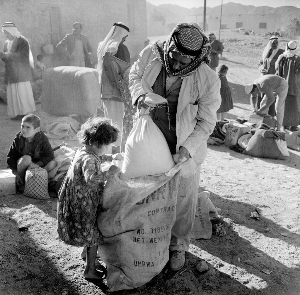 UNRWA Archive - Ausstellung Photobastei - BILDSEITE Ein Mann nimmt mit seiner Tochter in einer Verteilungsstelle in Aqaba, Jordanien, Rationen entgegen. In den 1950er-Jahren wurden die in und rund um Aqaba lebenden Flüchtlinge alle zwei Monate von UNRWA-Lastwägen mit Rationen versorgt, weil es in Aqaba selbst keine Flüchtlingslager gab. Nicht datiert © UNRWA-Archiv, Fotograf unbekannt