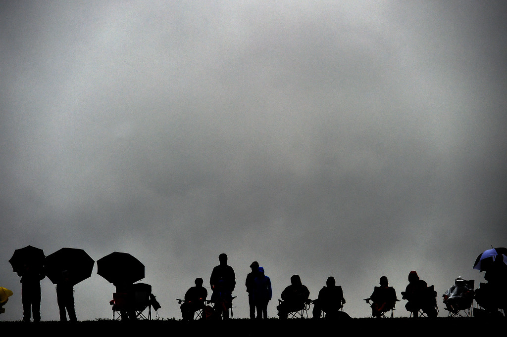 Spectators brave the rain to watch the Qualifying session ahead of the US Formula One Grand Prix at the Circuit of The Americas in Austin, Texas, on October 25, 2015. AFP PHOTO/JEWEL SAMAD