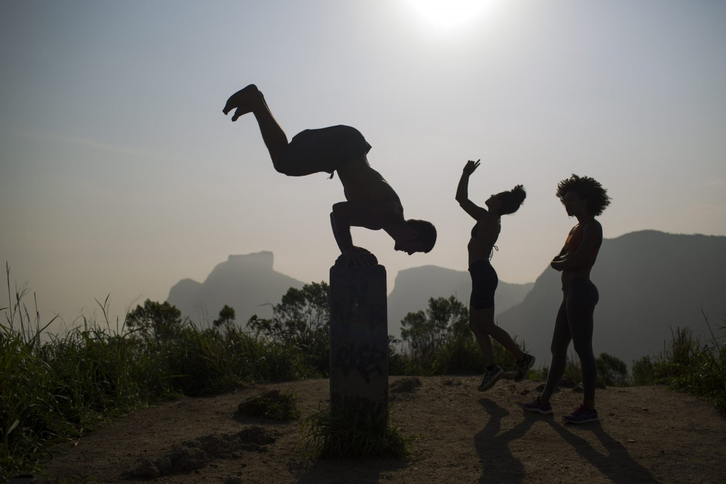 In this Friday, Oct. 2, 2015 photo, people exercise on the Morro Dois Irmaos or Two Brothers Mountain, atop the Vidigal slum in Rio de Janeiro, Brazil. Despite the recent wave of violence in other pacified favelas, Vidigal has been peaceful and is today a popular tourist spot. (AP Photo/Felipe Dana)