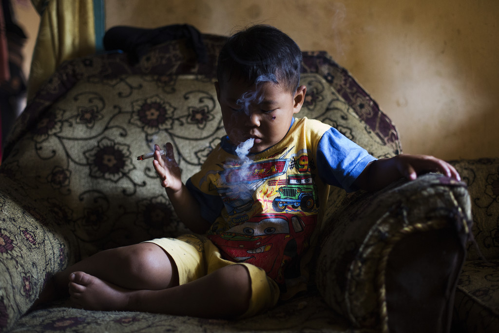 Five-year-old Ardian Azka Mubarok smokes at his home in Garut, Indonesia on March 27, 2015. (Photo By: Michelle Siu)