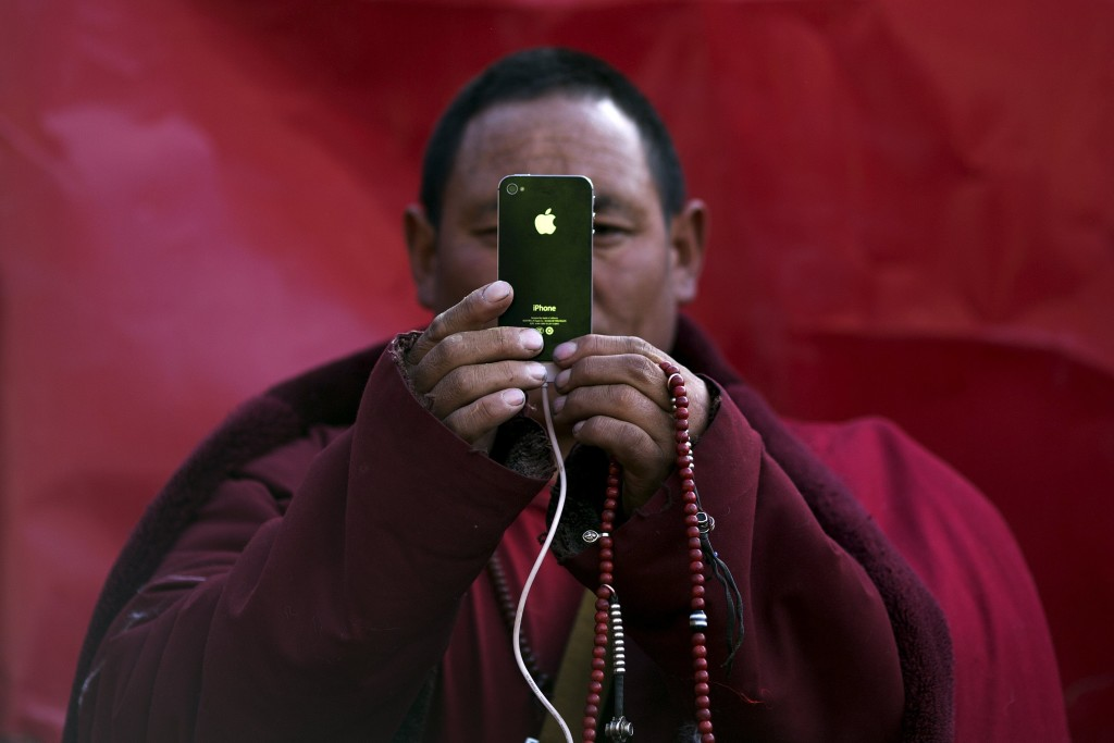 A Tibetan Buddhist monk take pictures with his smartphone of a daily chanting session at a Buddhist laymen lodge during the Utmost Bliss Dharma Assembly, the last of the four Dharma assemblies at Larung Wuming Buddhist Institute in remote Sertar county, Garze Tibetan Autonomous Prefecture, Sichuan province, China early October 30, 2015. The eight-day gathering of people chanting mantras and listening to teachings of monks starts every year around the 22rd of the ninth month on Tibetan calendar, the great day of Buddha's Descending from Tushita Heavens. The Larung Wuming Buddhist Institute, located some 3700 to 4000 metres above the sea level was founded in 1980 by Khenpo Jigme Phuntsok, an influential lama of Nyingma sect of Tibetan buddhism with only around 30 students but is now widely known as one of the biggest centres to study Tibetan Buddhism in the world. Picture taken October 30, 2015. REUTERS/Damir Sagolj TPX IMAGES OF THE DAY