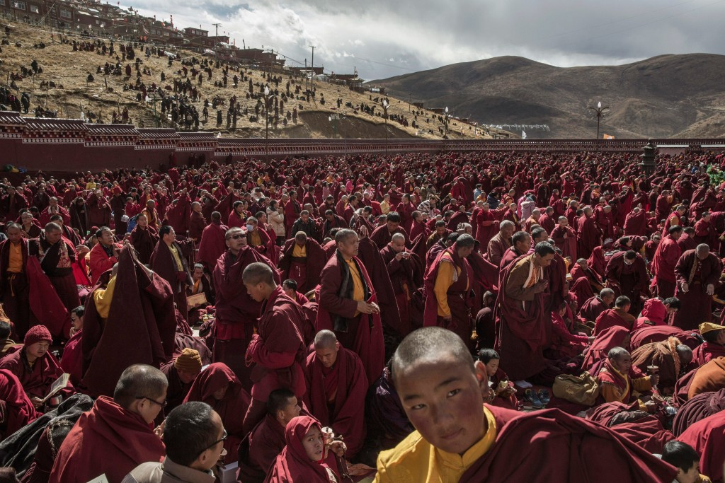 SERTAR, CHINA - OCTOBER 30: Tibetan Buddhist monks gather during a morning chanting session as part of the annual Bliss Dharma Assembly at the Larung Wuming Buddhist Institute on October 30, 2015 in Sertar county, in the remote Garze Tibetan Autonomous Prefecture, Sichuan province, China. The last of four annual assemblies, the week long annual gathering takes place in the ninth month of the Tibetan calendar and marks Buddha's descent from the heavens. Located high in the mountains of Sichuan, the Larung Wuming Buddhist Institute was founded in 1980 by an influential lama of the Nyingma sect and is widely regarded as the world's largest and most influential centres for Tibetan Buddhist studies. The school is home to thousands of monks and nuns and is popular for followers from all over the Tibetan areas and other parts of China. (Photo by Kevin Frayer/Getty Images)