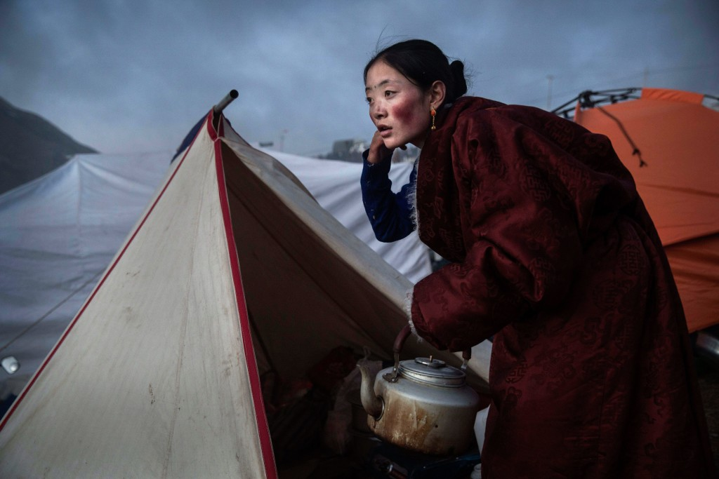 SERTAR, CHINA - OCTOBER 31: A Tibetan Buddhist nomad woman prepares tea at dusk following a chanting session as part of the annual Bliss Dharma Assembly at the Larung Wuming Buddhist Institute on October 31, 2015 in Sertar county, in the remote Garze Tibetan Autonomous Prefecture, Sichuan province, China. The last of four annual assemblies, the week long annual gathering takes place in the ninth month of the Tibetan calendar and marks Buddha's descent from the heavens. Located high in the mountains of Sichuan, the Larung Wuming Buddhist Institute was founded in 1980 by an influential lama of the Nyingma sect and is widely regarded as the world's largest and most influential centres for Tibetan Buddhist studies. The school is home to thousands of monks and nuns and is popular for followers from all over the Tibetan areas and other parts of China. (Photo by Kevin Frayer/Getty Images)